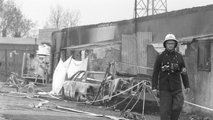 A fireman walks past burnt cars outside Bradford City's Valley Parade stadium, where 56 people died and 265 were injured as a fire swept the packed stand just before half-time of the game against Lincoln City in 1985