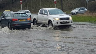 Cars drive through flood water