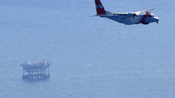 Plane from U.S. Coast Guard flies near an oil platform