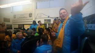 Sutton United manager Paul Doswell celebrates with his players at full time in the dressing room