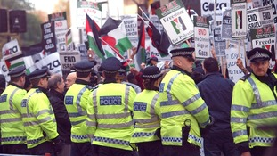 Police watch Pro-Palestinian demonstrators outside the Israeli Embass