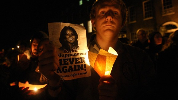 A protester holds a candle and poster with Savita Halappanavar's face on it