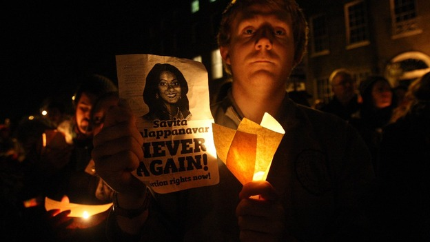 A protester holds a candle and poster with Savita Halappanavar&#x27;s face on it