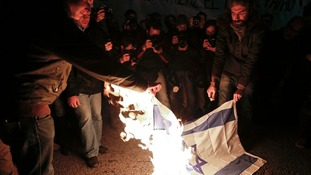 Demonstrators in Athens burn an Israeli flag