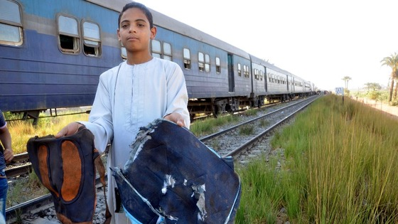 A boy holds school bags recovered from the site of a train crash