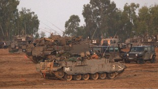An Israeli soldier sleeps atop an armoured personnel carrier near the border of the Gaza Strip