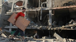 A Palestinian carries his belongings from a destroyed house after an Israeli air strike in the northern Gaza Strip