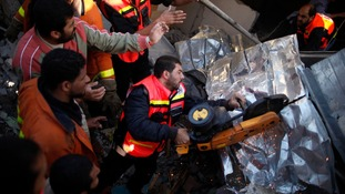 Palestinian Civil Defense members cut through metal as they search for victims under rubble