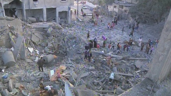 People walk through the rubble after a building housing international journalists is hit