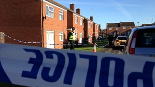 Police stand guard outside the house on Tadcaster Close