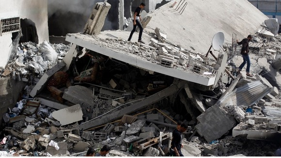 Palestinians walk amongst the rubble of destroyed house after an Israeli air strike in Gaza City