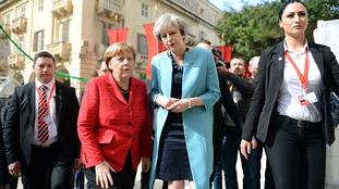 Theresa May and Angela Merkel talk during the walkabout.