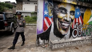 A police officer stands near a graffiti artwork welcoming President Barack Obama in Burma