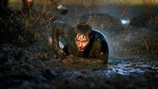 A competitor makes his way through Electroshock Therapy during the Tough Mudder event in Cheshire