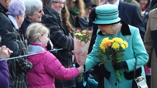 The Queen receives flowers from a young well-wisher.
