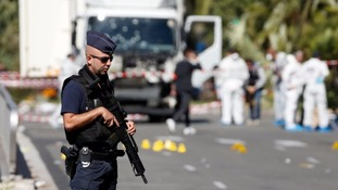 A policeman stands before the lorry used in the Bastille Day attack in Nice.