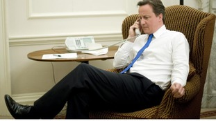 A library photo of David Cameron on the phone