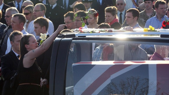 Mourners place flowers on the convoy of hearses in Carterton today.