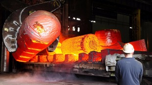 Red hot metal being moved across a heavy forge