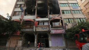 Officials inspect the damage after the Israeli strike in a building that houses media offices in Gaza City