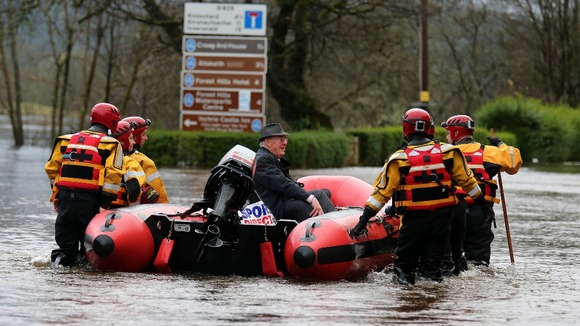 Firemen help a member of the public in Aberfoyle which has been flooded after the River Forth burst its banks.