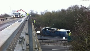 Crews remain at scene after lorry plunges from bridge