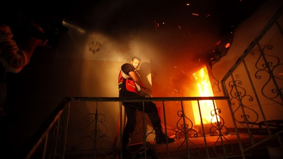 A Palestinian firefighter attempts to extinguish a fire in a building that also houses international media offices in Gaza city