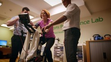 Reporter on exercise bike in lab