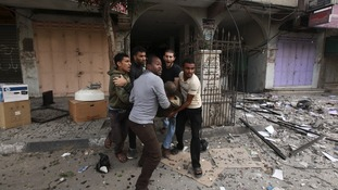 Palestinians evacuate a wounded man after an Israeli air strike on the floor of a building which houses media offices.