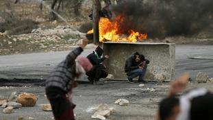 A Palestinian throws a stone using a sling shot at Israeli forces in the West Bank