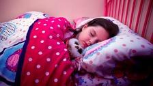 Girl asleep in bed.