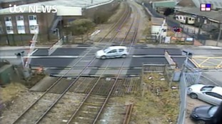 Watch: Driver swerves safety barriers at level crossing