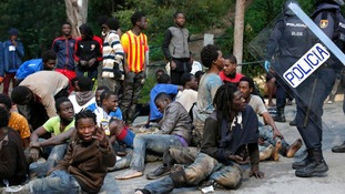 Migrants sit on the ground after storming a fence to enter the Spanish enclave of Ceuta