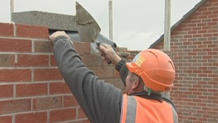 Laying bricks at the site of new homes