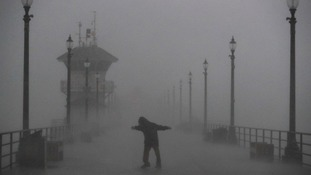 A man struggles along a pier in Huntingdon Beach.