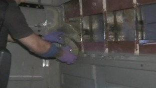 Drugs being removed from a hidden compartment in a lorry
