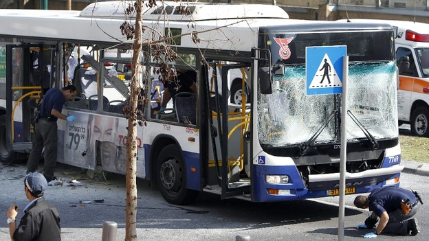Israeli police survey the scene after an explosion on a bus in Tel Aviv