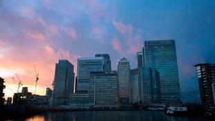 The sun sets behind Canary Wharf