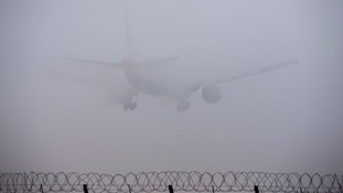 A plane lands in the fog