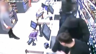 A knife wielding robber demands money from staff