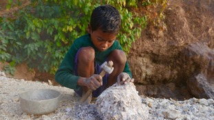 Six-year-old Shamil Murmu breaks rocks to fill his bowl with the prized mineral.