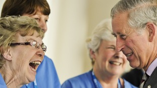 The Prince of Wales shares a joke with housekeeping assistant Roz Mesney at Dorset County Hospital