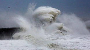 Waves crash over the harbour wall in Dover during a storm last year.