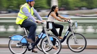 A man and woman ride the cycle hire scheme bikes.