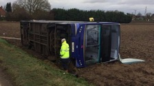 The X1 service in Cambridgeshire blew off the road and onto its side at around 1pm.