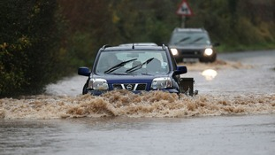 Cars make their way through floods in the village of Norton near Worcester