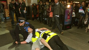 The comic character is restrained by the real Community Support Officer on Oxford Street