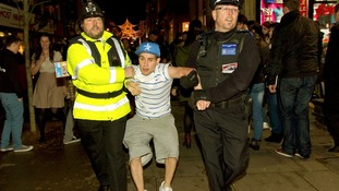 Lee Nelson's then carried off by the 'Policeman' and the CSO as the crowd looks on
