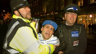 Lee Nelson is restrained by an actor playing a Policeman (on the left) and a real Community Support Officer