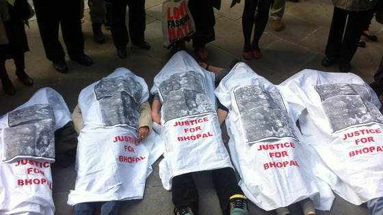 Protesters lie on the floor covered in sheets